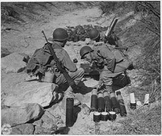 M1 carbine - 81 mm mortar crew in action at Camp Carson, Colorado, April 24, 1943. The soldier on the left has a slung M1 Carbine.