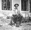 """85- letni Kramar Anton (Šmaškou) tolče s """"štampom"""" v posebnem lesenem možnarju (""""mrtau"""") tobak za njuhat 1951.jpg"""
