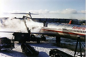Syracuse Hancock International Airport - An American Airlines McDonnell Douglas MD-80 being deiced at Terminal B. In the background is a Northwest Airlines DC-9 parked at Terminal A.