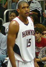 "A basketball player, wearing a white jersey with the word ""ATLANTA"" and the number 15 on the front, stands on a basketball court."