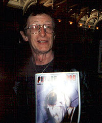 A photograph portrait of a man holding a comic book.