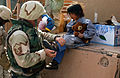 An airman fits a new pair of shoes on a young Bedouin girl in a village near Tallil Air Base.jpg