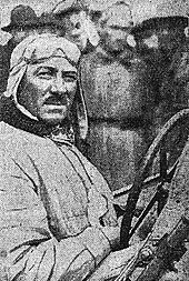 Photo d'André Morel posant au volant de sa voiture.
