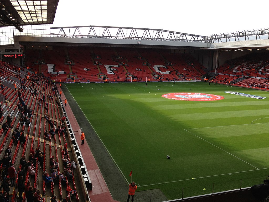 "A two-tiered stand which has red seats, there are also white seats which spell out ""L.F.C.. In front of the stand is a field of grass"