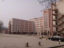 A large square with a fountain in the middle sits before several buildings with a pink rendering. The buildings are used for teaching as part of Anshan Normal University.