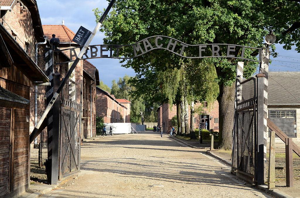 """La porte d'entrée du camp d'Auschwitz avec la promesse """"Arbeit macht frei"""" : Le """"travail rend libre"""". Photo de Marcin Białek."""