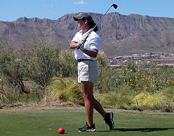 Golfer teeing off at the start of a hole