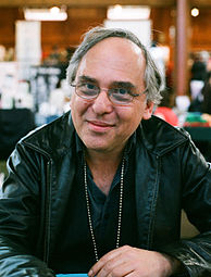 A late-middle-aged man with glasses, seated, wearing a black leather jacket, smiles at the camera.