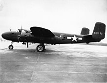 Black and white photo of an early bomber parked perpendicular to camera, facing left. Rearward of the wing is a star in front of horizontal stripes