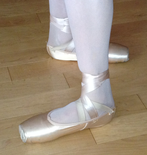 Positions of the feet in ballet - Open fourth position, with heels lined up, one directly in front of the other