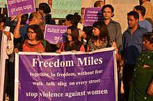 People carrying a banner marching in a protest against gang rape