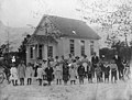 Bizzell Grove School, Wayne County, NC; ca 1900-1905. Students and teachers are posed in a group in front of a rural frame one-room school house. A handwritten ID label is affixed to the mounting (19084977632).jpg