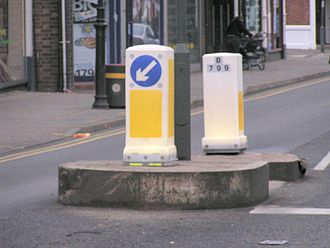 "Mandatory sign - A ""pass on the left"" sign embedded into an illuminated plastic bollard in the United Kingdom."