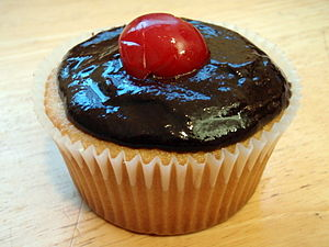 Boston cream cupcake topped by a cherry.