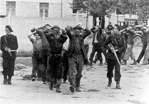 Milice - Resistance members captured by the Milice, July 1944. One of the miliciens is armed with a captured British Sten gun.