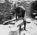 COLLECTIE TROPENMUSEUM Een Samo vrouw bezig met de bereiding van gierstepap TMnr 20010231.jpg