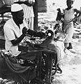 COLLECTIE TROPENMUSEUM Een kleermaker naait kleding op zijn Singer naaimachine TMnr 20010540.jpg