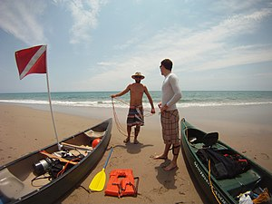 Canoe and Kayak diving - Two canoe divers preparing their scuba equipment and safety devices on a beach.