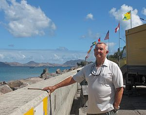 Arthur Anslyn - Captain Arthur Anslyn in 2014, on the waterfront next to the port, in Charlestown, the capital of Nevis, West Indies. Nevis flag flying in upper right of image. Southeastern Peninsula of the Island of St. Kitts visible in the distance.
