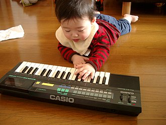 Electronic keyboard - A child playing a Casio keyboard with small-size minikeys.