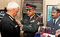 Col. Narendra Singh of Kendriya Sainik Board, pinning a lapel on the Chief of Naval Staff, Admiral Sunil Lanba, on the occasion of the Armed Forces Flag Day, in New Delhi on December 07, 2016.jpg