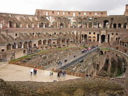 An interior of the Colosseum. The partial floor is a modern reconstruction; below are the underground vaults and tunnels originally used to house animals and slaves.
