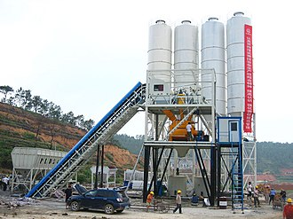 Concrete plant - In this photo, you can see a set of belt conveyor concrete plant being installed. It clearly shows the belt conveyor concrete plant's main structure, batch hopper, belt conveyor, cement bins, mixer, etc.