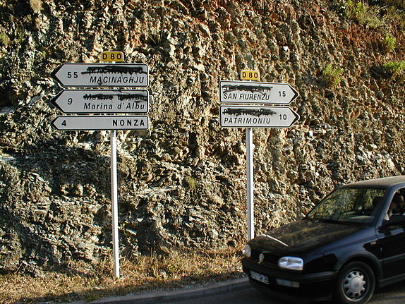 Bilingual road-signs, with official (IGN) French names (often in Italian) being crossed out by some local nationalists. Corsican nationalism.jpg