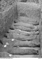 The bodies of nine soldiers wrapped in hessian, laid out in the bottom of a mass grave