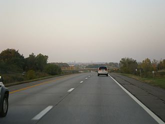 Interstate 390 - Northbound on I-390 in southern Henrietta. The skyline of downtown Rochester is visible in the background.
