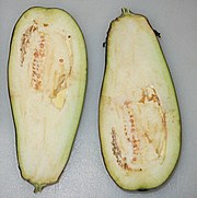 A purple aubergine which has been sliced in half, showing the inside. The flesh surrounding the seeds is already beginning to oxidize and turn brown just minutes after slicing.