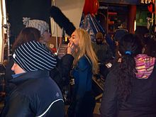 Blond woman having make-up applied on a movie set, surrounded by busy people.