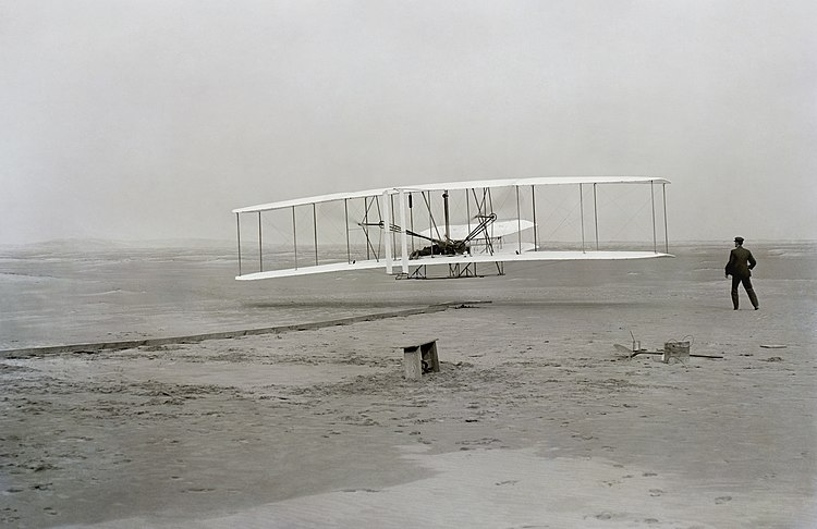 First successful flight of the Wright Flyer, by the Wright brothers. The machine traveled 120 ft (36.6 m) in 12 seconds at 10:35 a.m. at Kill Devil Hills, North Carolina. Orville Wright was at the controls of the machine, lying prone on the lower wing with his hips in the cradle which operated the wing-warping mechanism. Wilbur Wright ran alongside to balance the machine, and just released his hold on the forward upright of the right wing in the photo. The starting rail, the wing-rest, a coil box, and other items needed for flight preparation are visible behind the machine. This is described as
