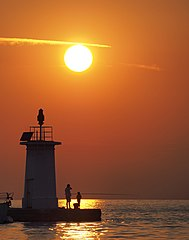 Fishing by lighthouse at sunset (Adriatic Sea).jpg