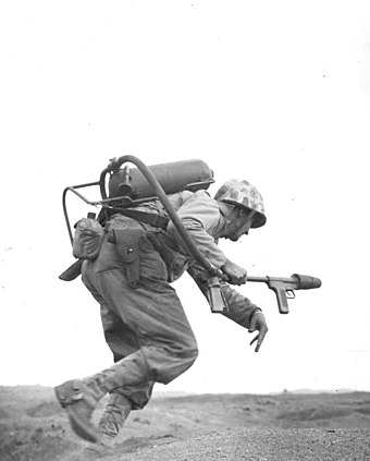 A flamethrower operator of E Company, 2nd Battalion 9th Marines, 3rd Marine Division, runs under fire on Iwo Jima. Flamethrower-iwo-jima-194502.jpg