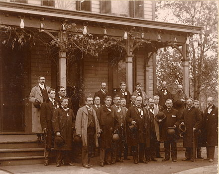 A formative shot taken in front of an ornate colonial-style home. A middle-aged gentleman with thinning hair stands at center of a group of about fifteen men.