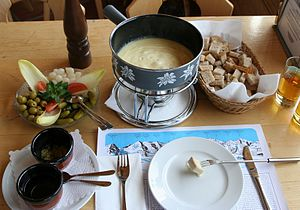 Fondue - A full cheese fondue set in Switzerland.  Apart from pieces of bread to dip into the melted cheese, there are side servings of kirsch, raw garlic, pickled gherkins, onions, and olives.