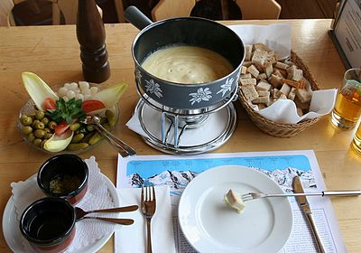 Fondue is melted cheese, into which bread is dipped Full cheese fondue set - in Switzerland.JPG