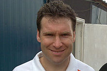 A headshot of a Caucasian man with brown hair in a white polo shirt.