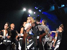 Medium range shot of a group of people, wearing black-and-white colored dress on stage. Central to them is a blond woman, wearing black bordered glasses, being held up by a man. Lights fall on the stage from above.