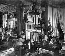 A black and white photograph of a well-decorated room with a globed hanging light fixture. On the left is an entryway to a neighboring room, similarly decorated