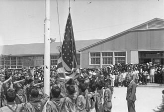 Japanese-American service in World War II - Boy Scouts at the Granada War Relocation Center raise the flag to half-mast during a Memorial Service for the first six Nisei soldiers from this Center who were killed in action in Italy. The service was attended by 1,500 Amache internees. -- August 5, 1944.