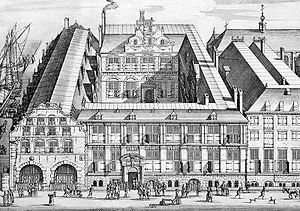 "Financial centre - 17th-century etching of the Oost-Indisch Huis (Dutch for ""East India House""), the headquarters of the United East India Company (VOC) in Amsterdam. Considered by many to be the first multinational corporation, the VOC - the first company to be listed on an official stock exchange - started off as a spice trader. The VOC's institutional innovations helped lay the foundations for modern corporations (especially large-scale business enterprises or multinational corporations) and capital markets that now greatly affect the world economy."