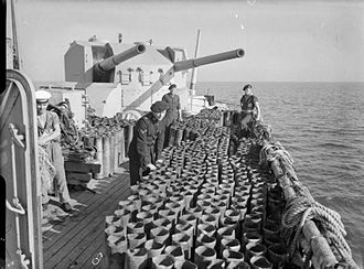 QF 5.25-inch naval gun - 5.25 in dual turret on HMS Sirius. A large number of empty cartridge cases stand on the deck in foreground, fired in support of the Allied invasion of Normandy, June 1944