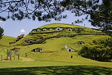 "Image shows rolling green hills with dwellings built in to them. These formed the town of ""Hobbiton"" in the Lord of the Rings films. These and other sets were constructed in the town of Matamata, in the Waikato region of New Zealand's North Island."