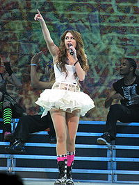A brunette teenager singing into a microphone. She is facing up and pointing with her index finger. She is wearing a short white dress with a tutu bottom. Behind her are background dancers and graffiti projected on a screen.