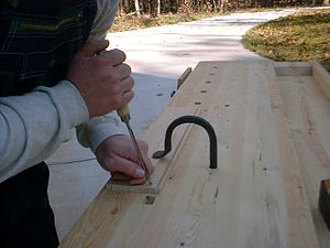 hold fast being used to affix a board to the benchtop for chiseling ...