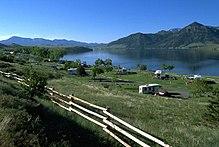 Widok na ciemnoniebieskie jezioro otoczone niskimi górami