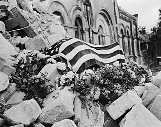 Thomas D. Howie - Howies flag draped body on the rubble of the St. Croix Cathedral in St. Lo