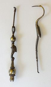 Two long, thin metal objects. The right object resembles a double-ended dentist pick in the shape of a crane bird. Its legs form the lower half, ending in a small pick; the body and wings form the handle in the middle; whereas the curved neck, head and long pointed beak form the upper pick. The left object is straight; a thin twisted rod ends in a large ball, followed by a fish motif again bounded by a ball, and ending in a crown with its peaks pointing inwards, presumably to hold bristles.
